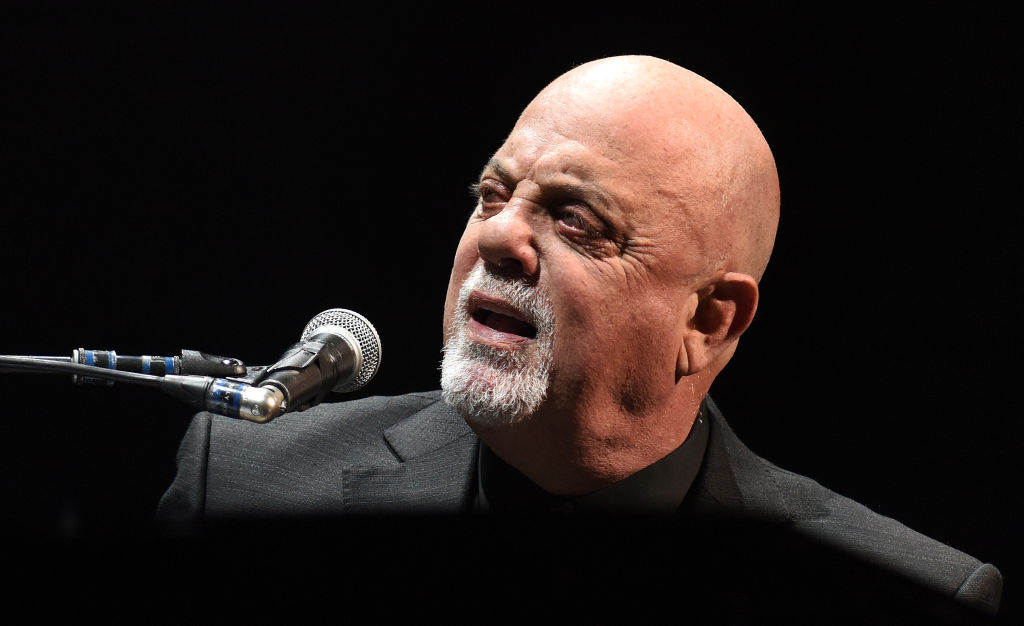 billy joel singing into a microphone