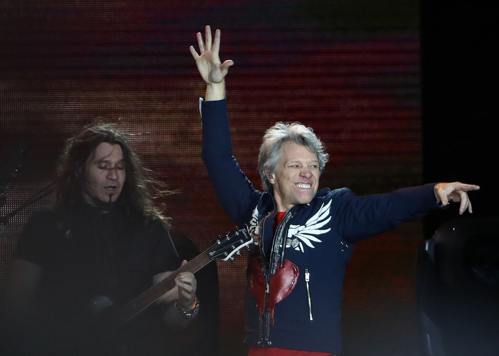 bon jovi on stage pointing and dancing