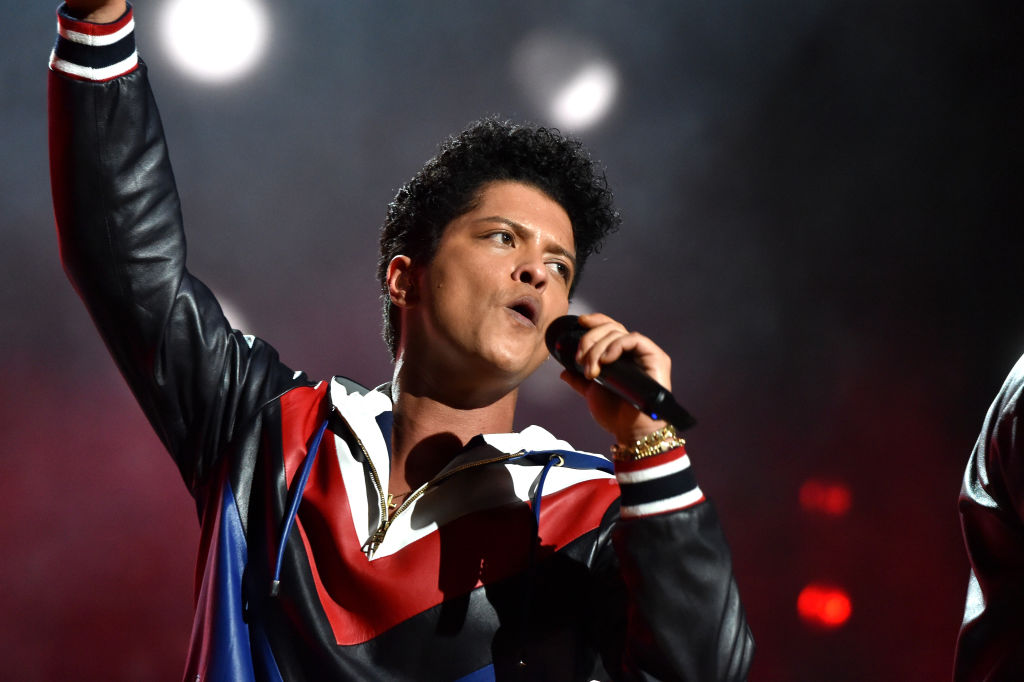 bruno mars singing into a microphone on stage