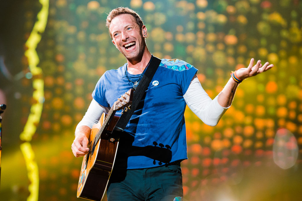chris martin of coldplay singing on stage with his guitar