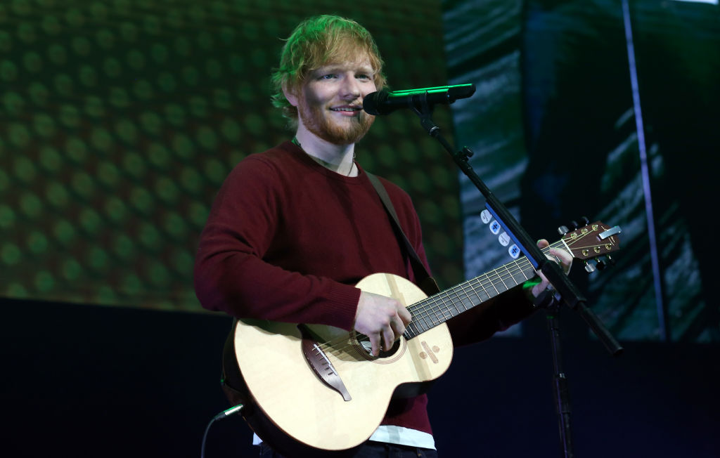 ed sheeran singing into a microphone and playing a guitar on stage