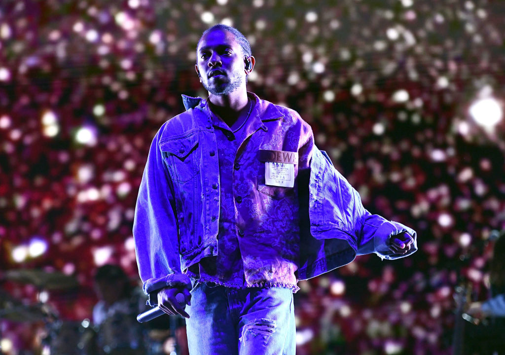 kendrick lamar on stage holding a microphone
