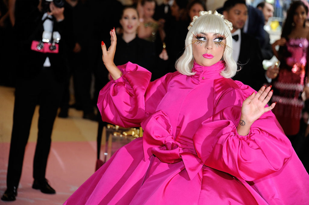 lady gaga at the met gala dressed in a big pink dress and sparkly eyelashes