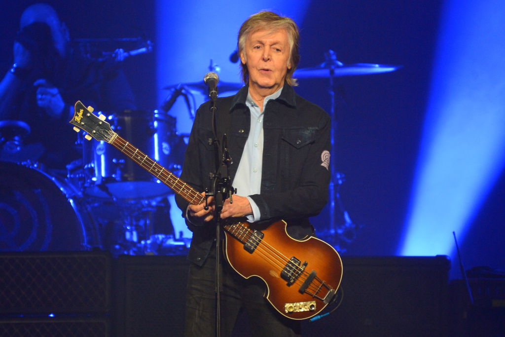 paul mccartney singing and playing the guitar on stage