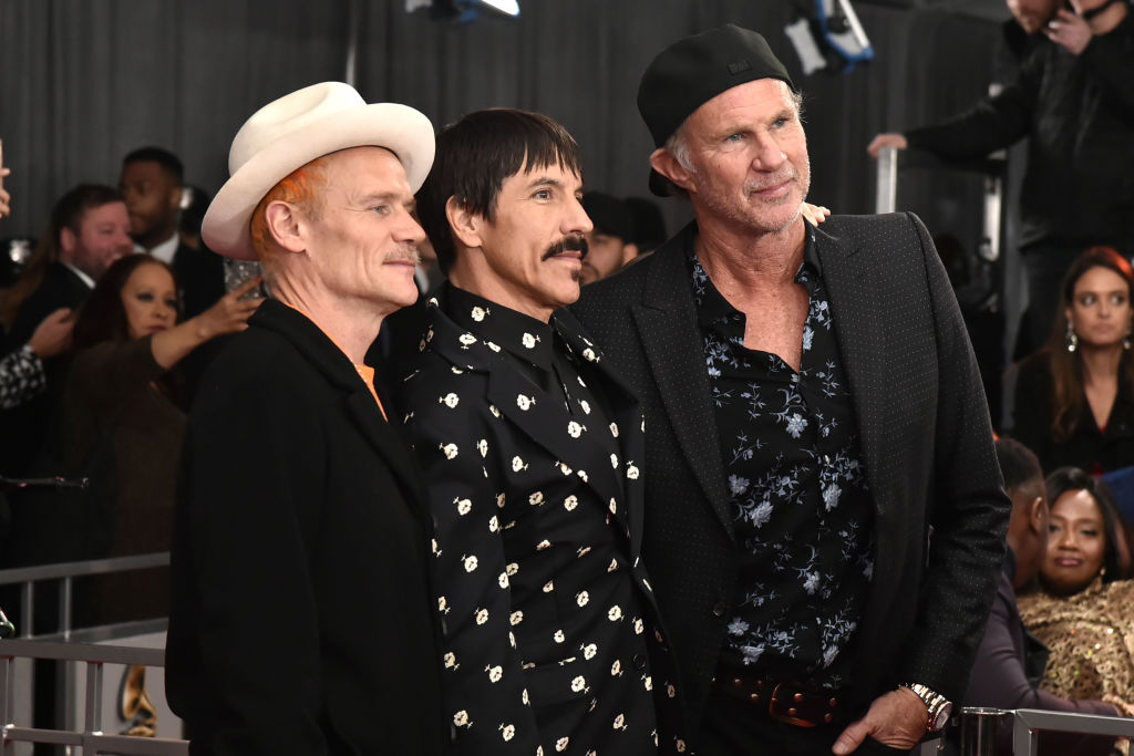 red hot chili peppers posing for a group photo at a red carpet event