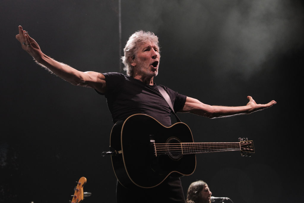 roger waters singing on stage with his guitar