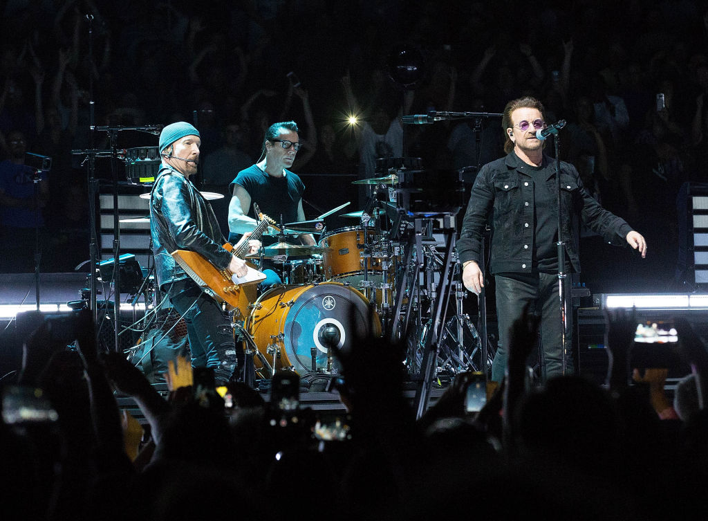 u2 band members on stage playing a concert