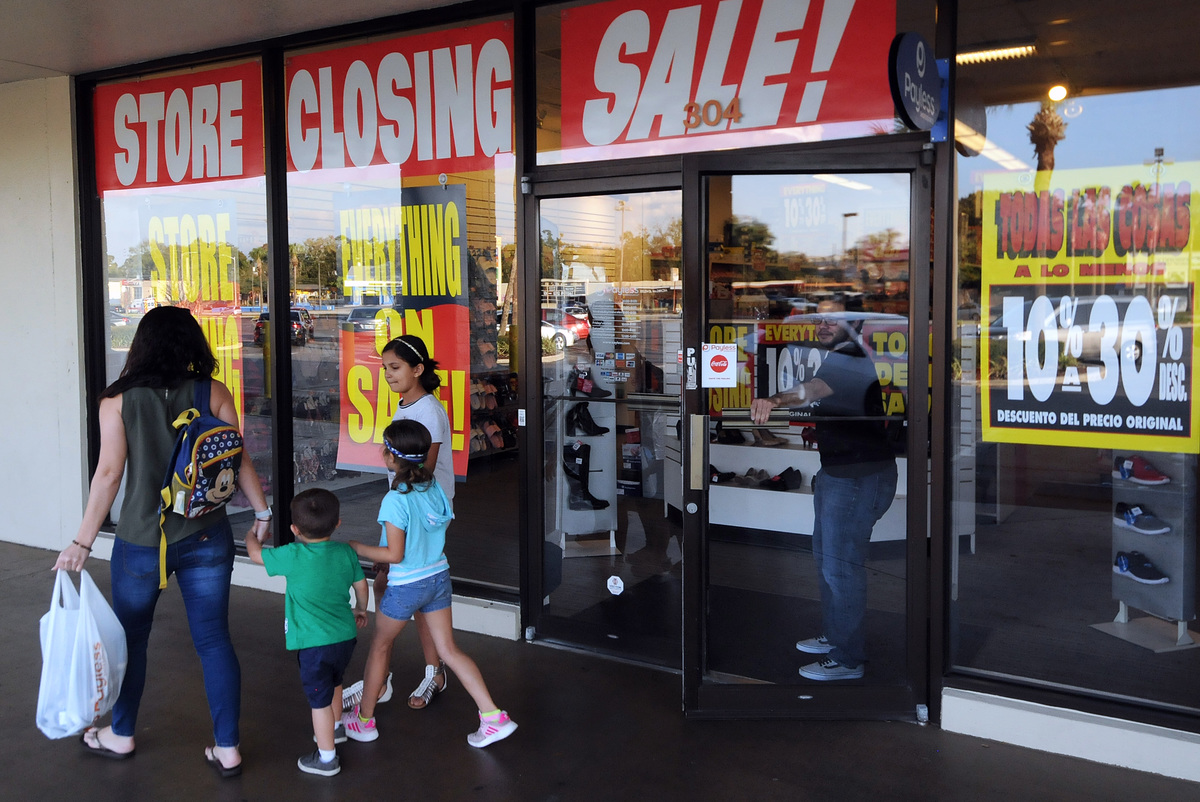 Shoppers leave a Payless ShoeSource store on the first day of the firm's liquidation sale after confirming