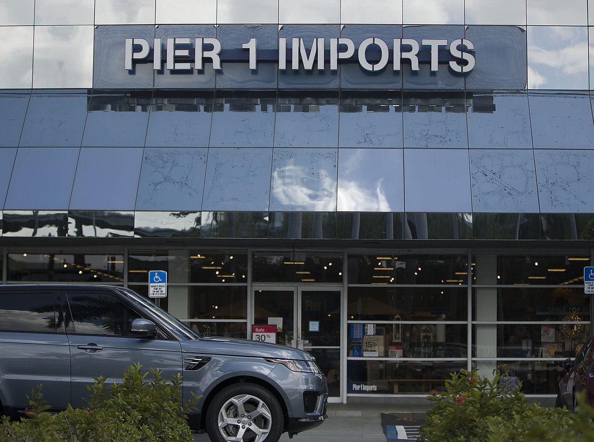 A Pier 1 Imports store closing with a car in front of it