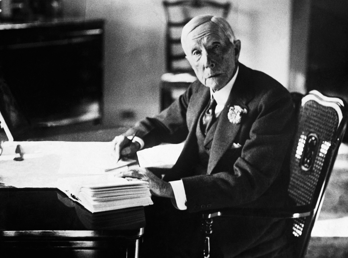 John Davidson Rockefeller (1839-1937), the American oil magnate and philanthropist sits writing at his desk.