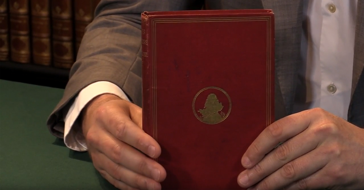 close up of a man holding alice's adventures in wonderland first edition