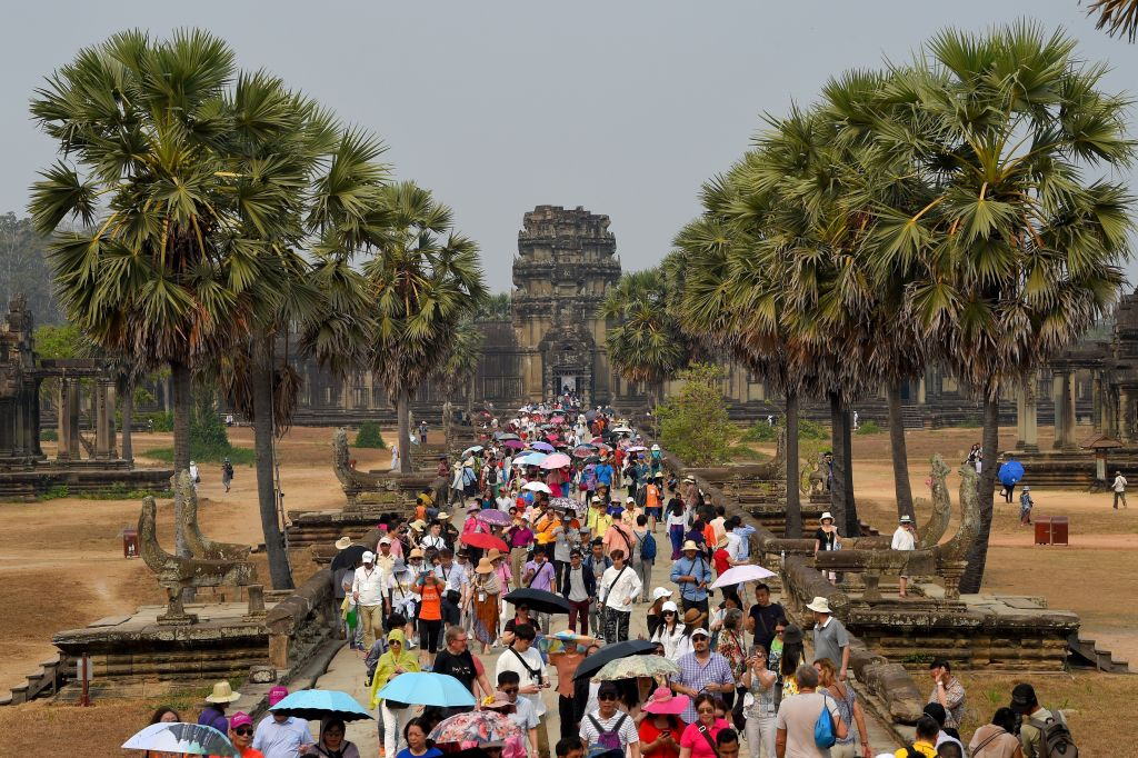 front view of angkor wat temple in cambodia with people in the walkway