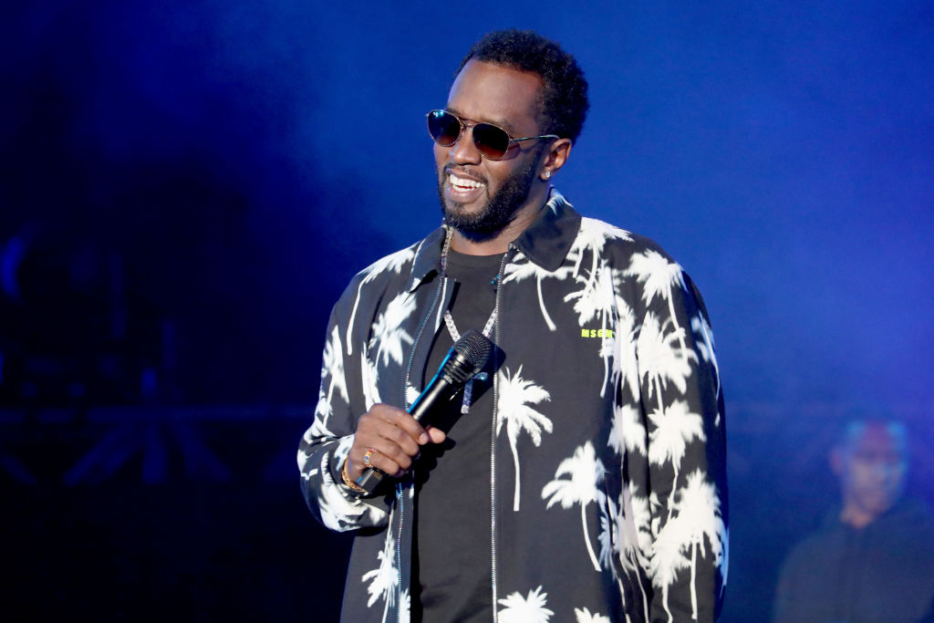 diddy singing on stage with a microphone and sunglasses