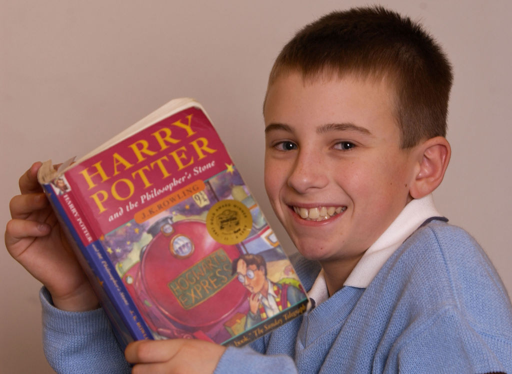 young boy smiling and holding harry potter book