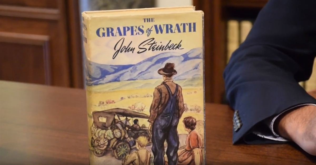 the grapes of wrath book on a wooden table