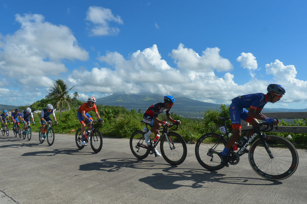 bicyclists ride through the landscape of a cloudy sky, mountain, and palm trees in the philippines