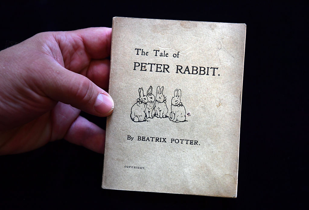 close up of a hand holding the tale of peter rabbit first edition