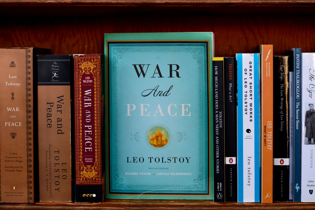 various copies of war and piece lined up on a bookshelf