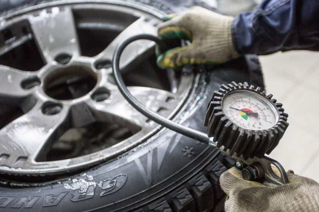 GettyImages-1055235330 Checking tire pressure on a car fitted with winter tyres.