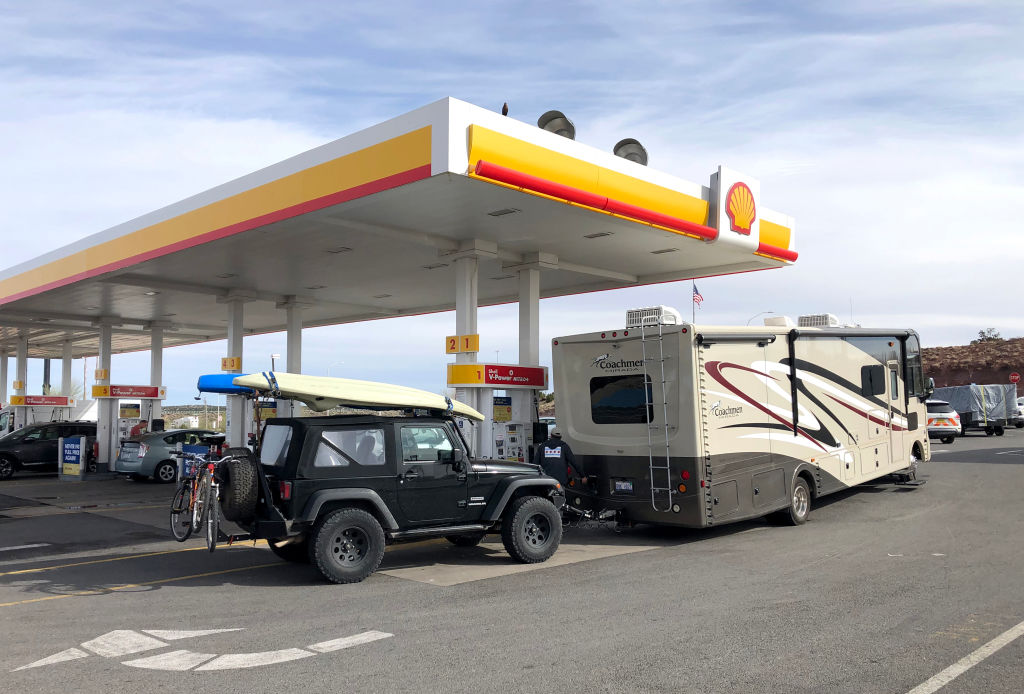 GettyImages-1140674359 gas station A recreational vehicle stops for gas and is fully prepared for a road trip with an RV, Jeep, Kayak and bicycles