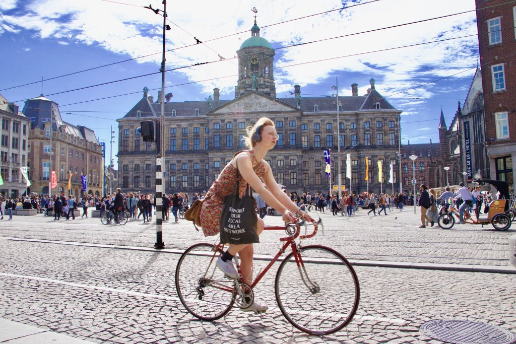 GettyImages-1147419894 A woman rides a bicycle in a street in Amsterdam, Netherlands