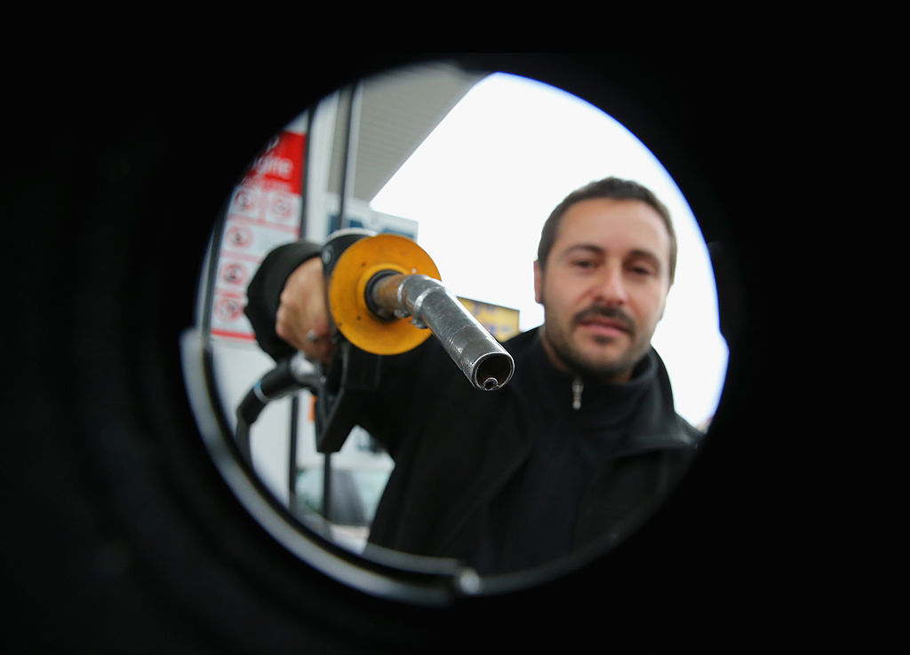 GettyImages-174263786 In this photo illustration, a man uses a fuel dispenser to fill his car up with petrol at a petrol station