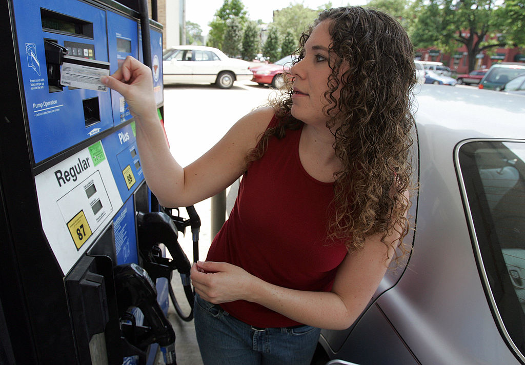 GettyImages-74229904 Amy Foley of Washington, DC, swipes her credit card as she prepares to fill her car with gas at an Exxon station