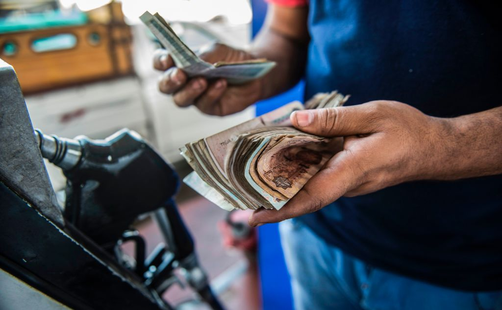 GettyImages-803378948 An Egyptian petrol station worker counts cash collected from customers, in the capital Cairo on June 29, 2017. Egypt ann