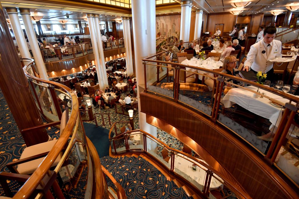 Passengers eat lunch in the Brittania restaurant of the Cunard cruise liner RMS Queen Mary 2 sailing in the Atlantic ocean during the Bridge 2017, a transatlantic race between the cruise liner and the world's fastest Ultim trimarans from Saint-Nazaire, France, to New York City, USA on June 26, 2017-812331916