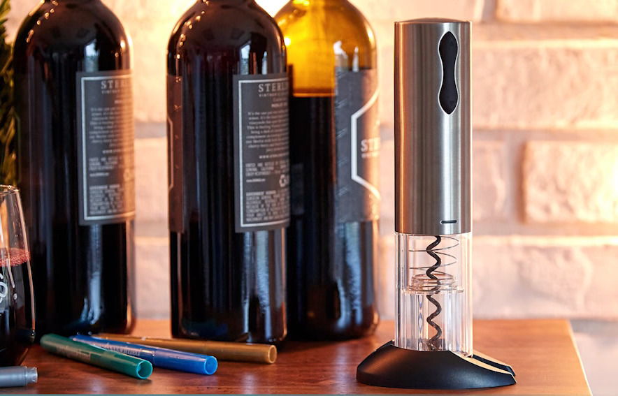 Electric wine opener sits to the right of red wine bottles