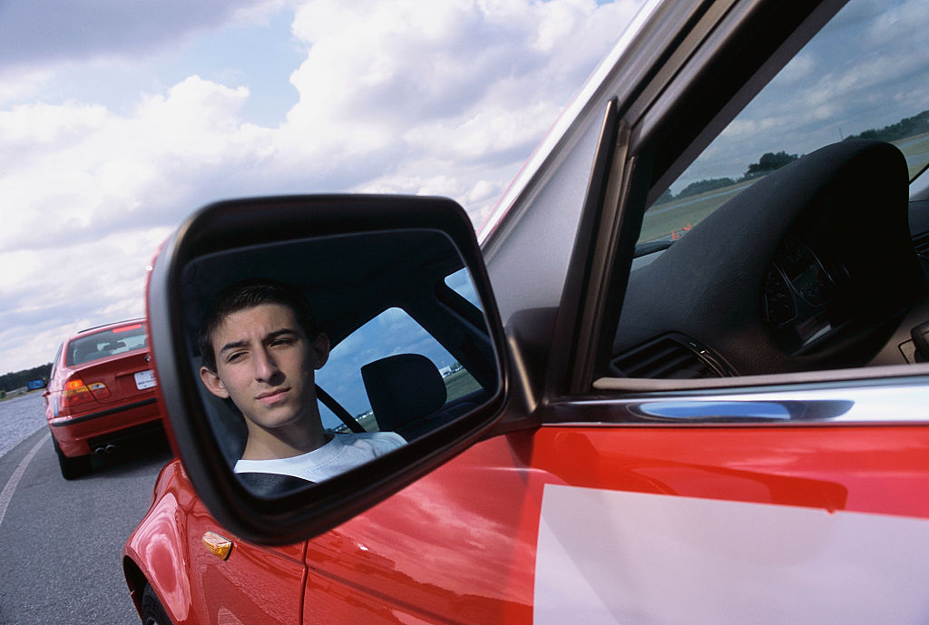 a teenager pictured in a red car