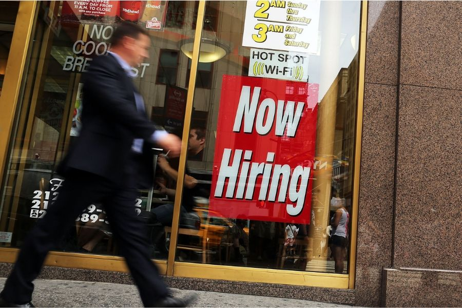 A man walks by a now hiring sign in the window