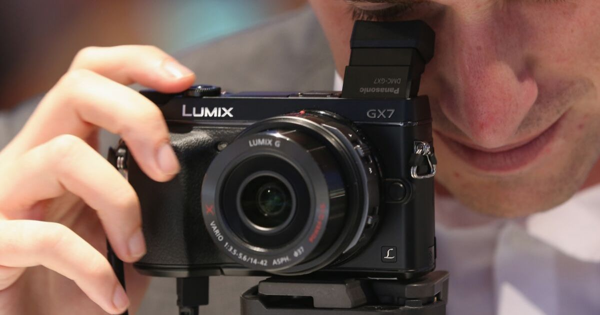 A host looks through a Lumix GX-7 digital camera on display at the Panasonic stand at the IFA 2013 consumer electronics trade fair