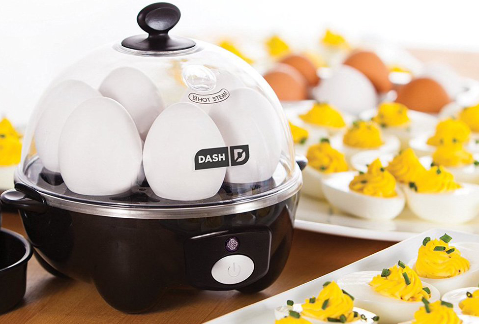 Black egg cooker surrounded by deviled eggs