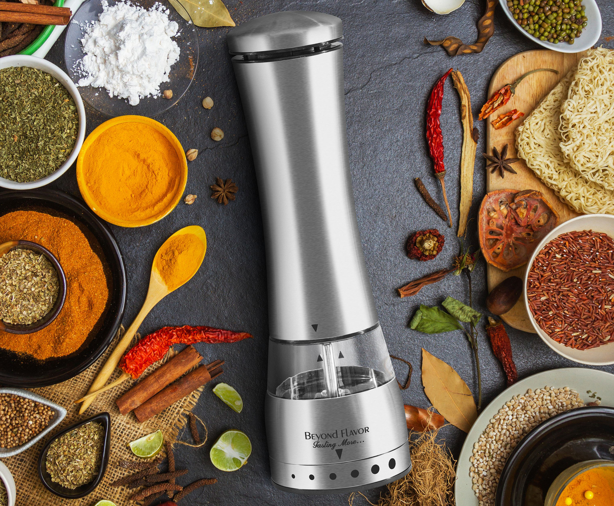 Electric pepper mill surrounded by spices