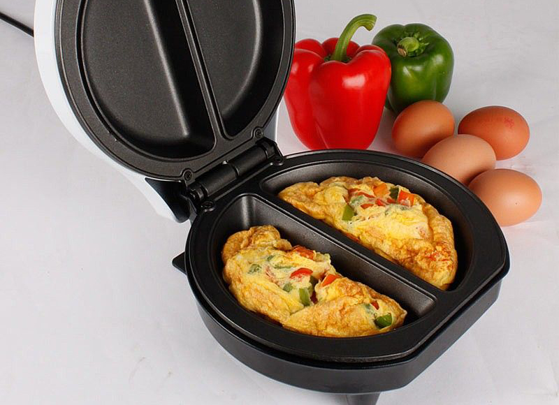 Electric omelette maker with eggs and peppers next to it