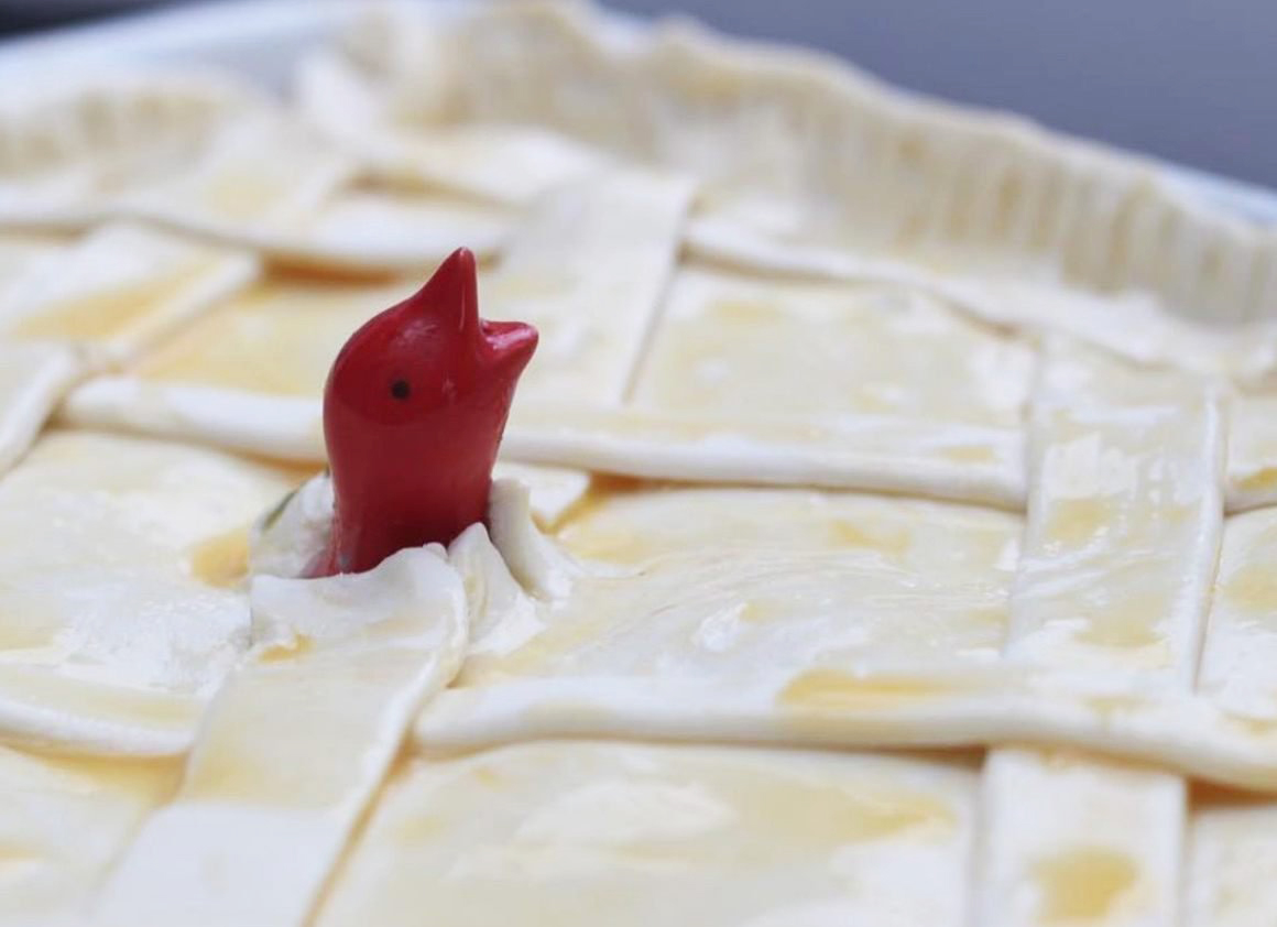 Red pie bird poking out of a pie crusts
