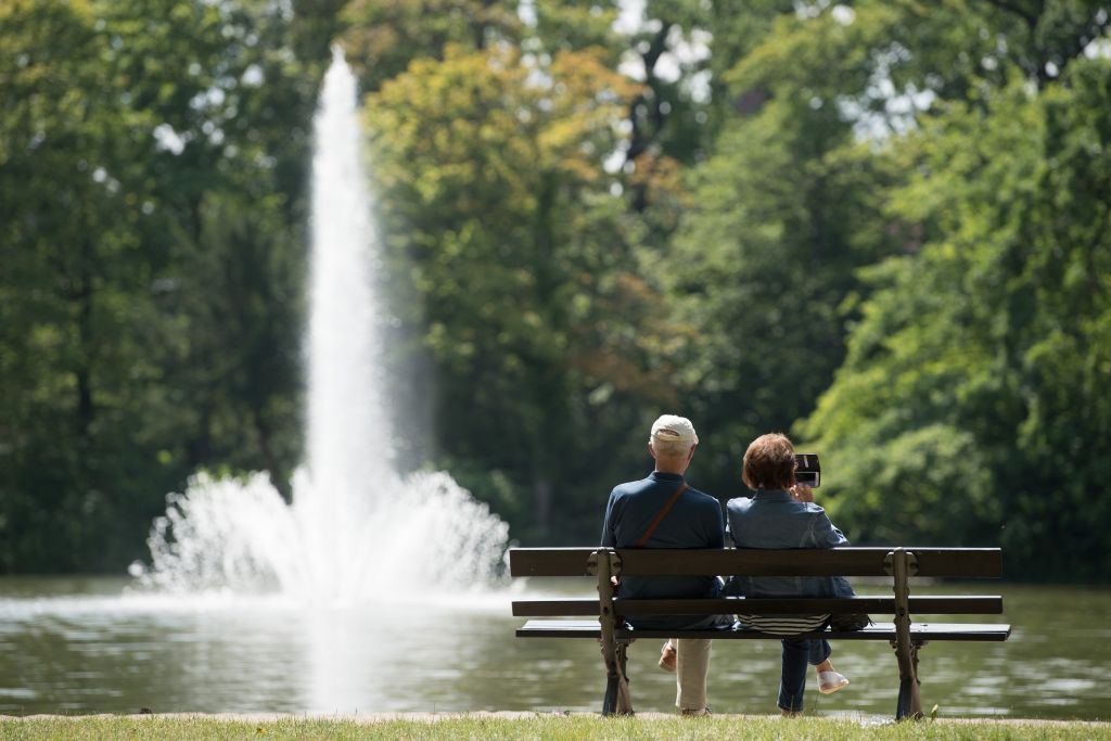 retired couple sits on a bench at Lake Carola