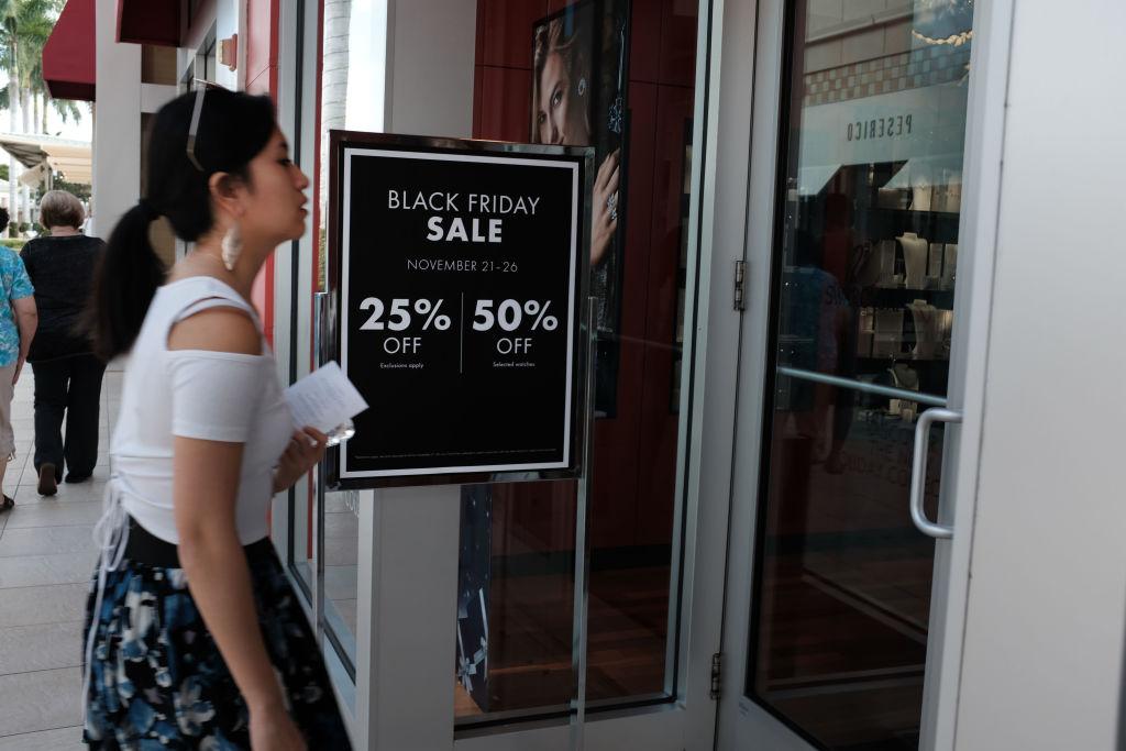 A shopper walks past a 'Black Friday Sale' sign