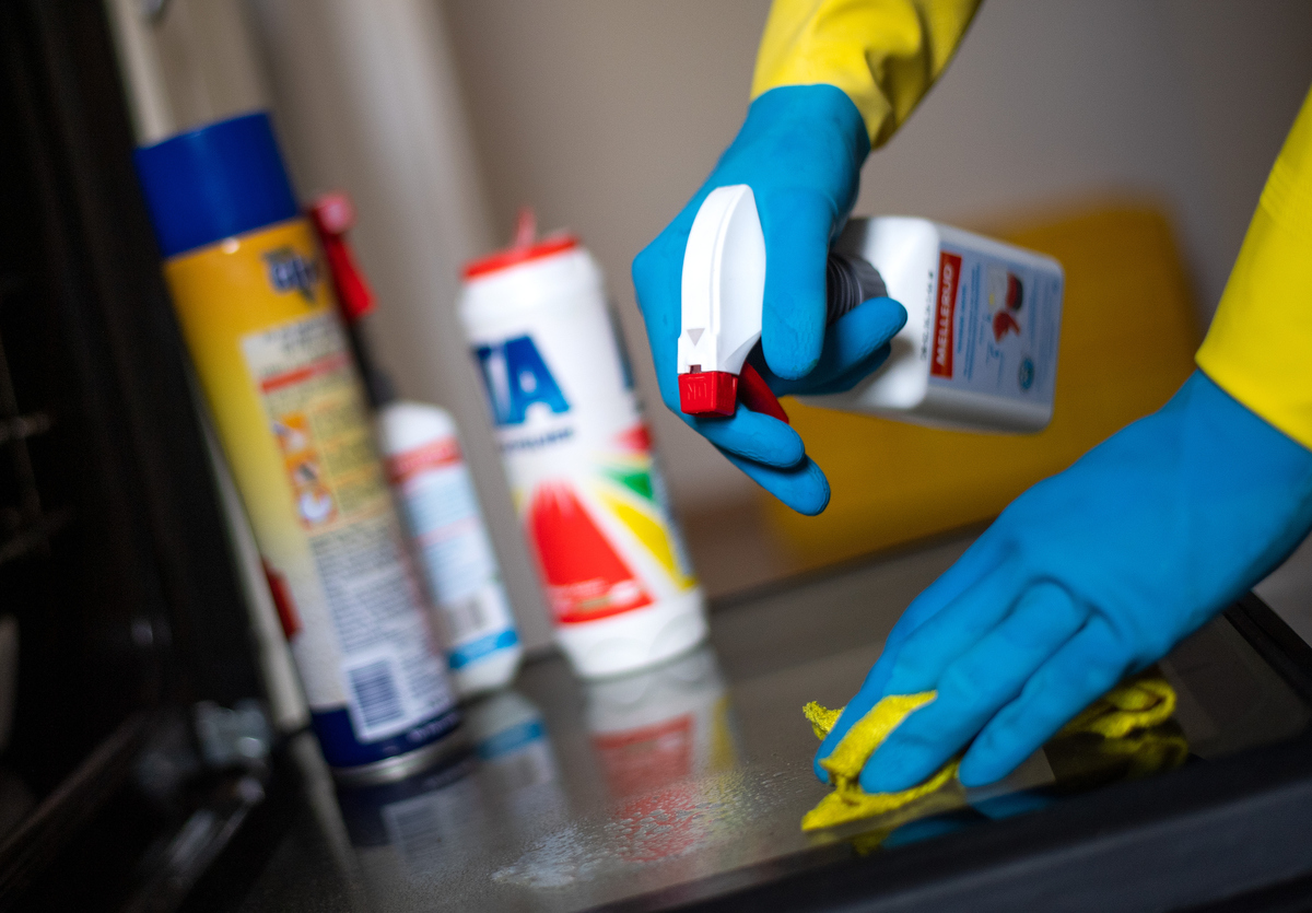 A man in rubber gloves cleans a glass surface.
