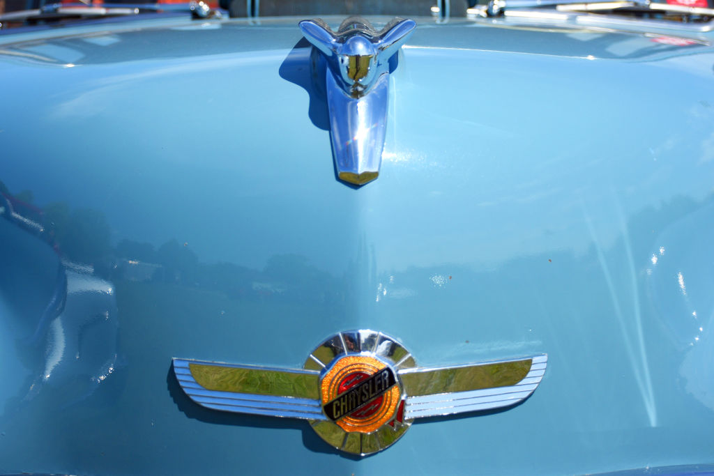 A closeup of a vintage Chrysler shows its logo.