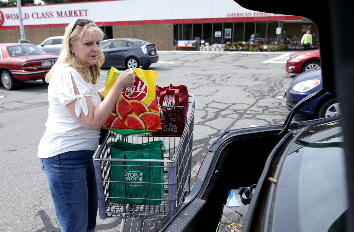 Shopper packs her car after shopping at The Big Y grocery store