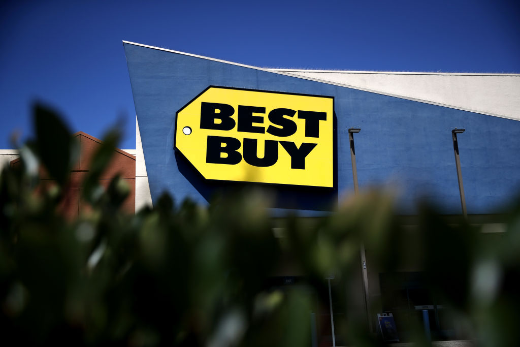 A Best Buy sign is photographed from behind a hedge.