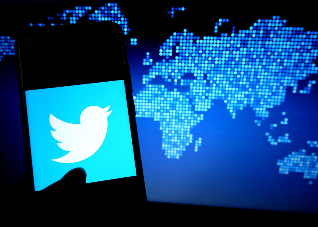 A silhouette shows a phone illuminated by the Twitter logo.