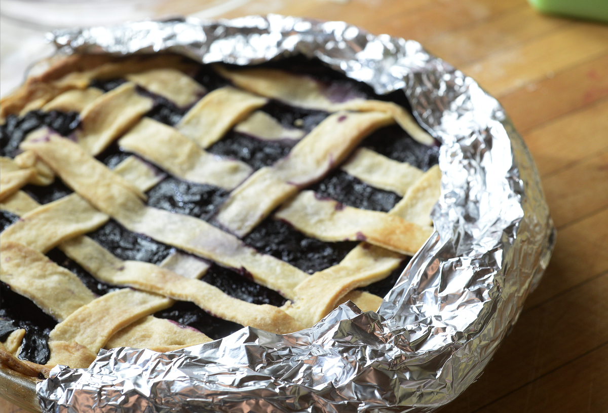 A pie is lined with aluminum foil around the edge of the crust.