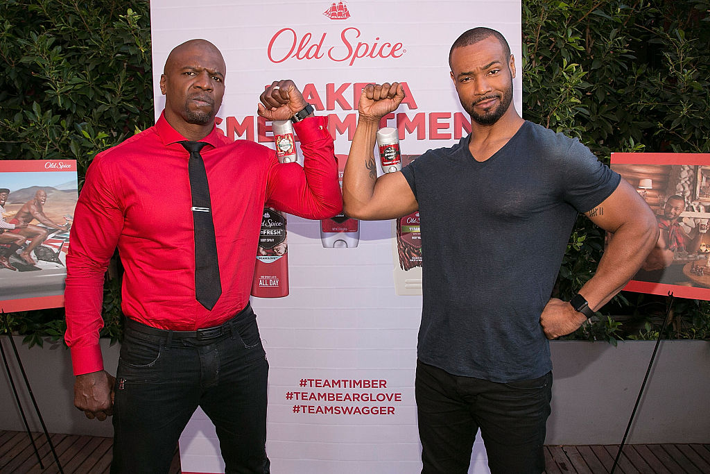 Terry Crews and Isaiah Mustafa flex their biceps in front of an Old Spice ad.