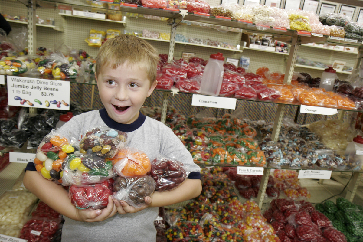 A boy excitedly holds bags of candy at Wakarusa Dime Store.
