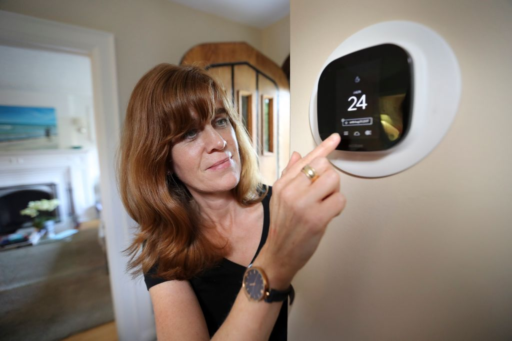 woman with smart thermostat