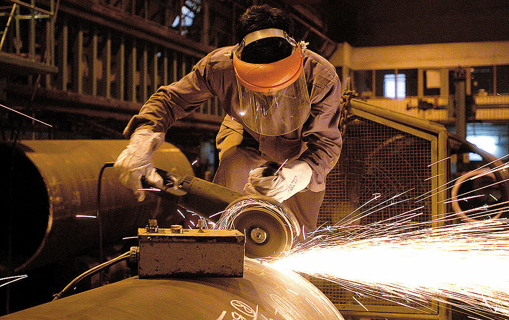 A Thermax employee works on a metal instrument.