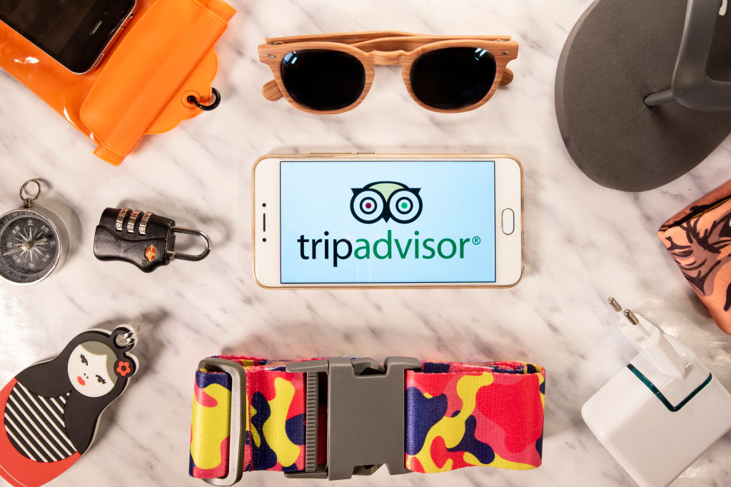 Items on a counter are laid out beside a phone that displays the trip advisor logo.